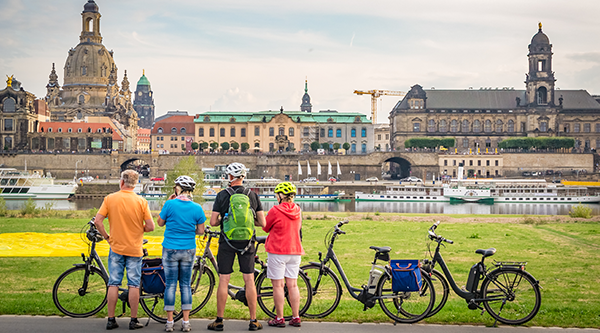 Group of cyclists on the banks of the river Elbe, in the background the silhouette of Dresden - © The Photographer – stock.adobe.com