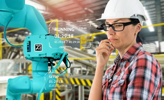 Photomontage: Woman with construction helmet and smart glasses looks at industrial robot, context information from the data glasses is superimposed