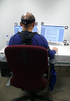 Test person equipped with measurement system working at two screens