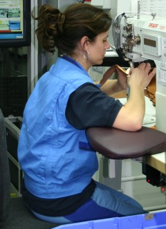 Sewing operative working in seated position at the modiefied workplace