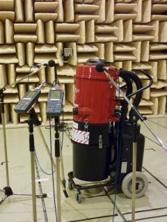 Industrial vacuum cleaner in front ot the sound-attenuating wall