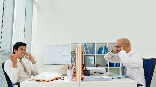 Ein Mann im Büro telefoniert und lacht, der Kollege hält sich die Ohren zu