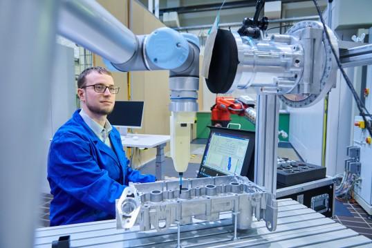 IFA-Wissenschaftler mit Roboter und Kraftmessvorrichtung
