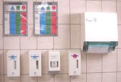Nebeneinander an der Wand hängend: Hautschutzplan, Seifen und Pflegemittel und Handtuchrolle