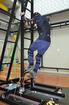 Test subject equipped with the CUELA measurement system on a ladder in the laboratory