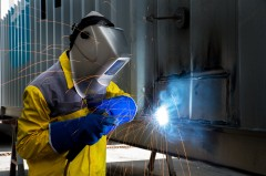 Welder with protective clothes and shield