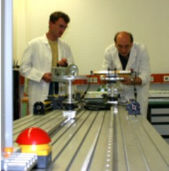 Two persons standing at the test bench
