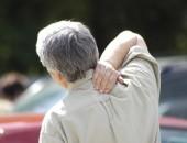 Bild eines Mannes, der sich rückseitig an die Schulter fasst