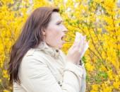 Bild einer Frau, die in ein Taschentuch niest
