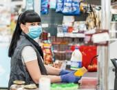 Frau an einer Kasse mit Mundschutz