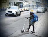Kind auf Roller und Auto im Straßenverkehr