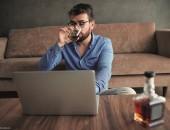 Bild eines Mannes mit Alkohol vor dem Laptop
