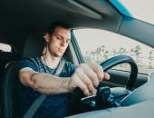 Bild eines Autofahrers, der bei der Fahrt die Augen schließt