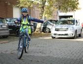 Kind auf Fahrrad und Auto im Hintergrund