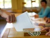 Bild einer Hand die einen Wahlzettel in die Wahlurne wirft