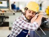 Foto: Müder Arbeiter lehnt an Maschine