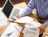 Person am Schreibtisch mit Formularen