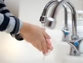 Kinderhände unter Wasserhahn beim Händewaschen