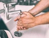 Frau mit Mund-Nase-Schutz und Hände beim Händewaschen