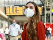 Foto: Frau mit Nase-Mund-Bedeckung in einem Bahnhof