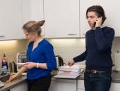 Foto: Küche: Frau bei Hausarbeit und Mann am Telefon im Homeoffice