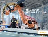 Foto: Arbeitnehmer und Roboter mit dem Logo des Deutschen Arbeitsschutzpreises 2021
