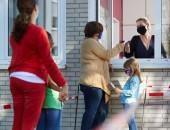 Foto: Abstand und Maskentragende vor einer Grundschule