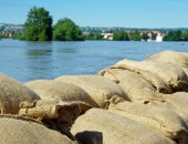 Foto: Sandsäcke an einem Hochwasser führenden Fluss