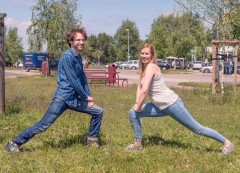 two people make stretch exercises on a meadow