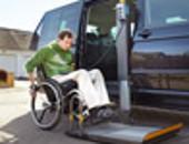 Mann im Rollstuhl steigt mittels eines Hublifts in einen UV-Bus (Bildarchiv DGUV)