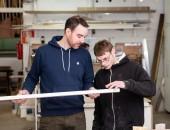 Ein junger Mann hilft einem Jungen mit einer Behinderung bei der Arbeit; zeichensetzen Medienagentur / Harms